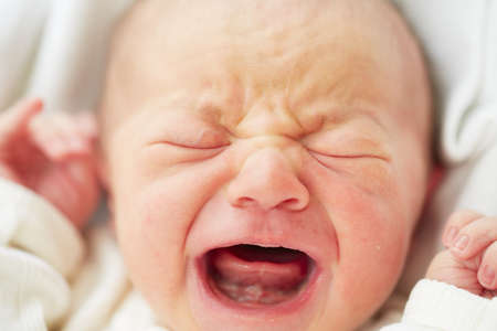infant hand: Newborn baby is crying - selective focus Stock Photo
