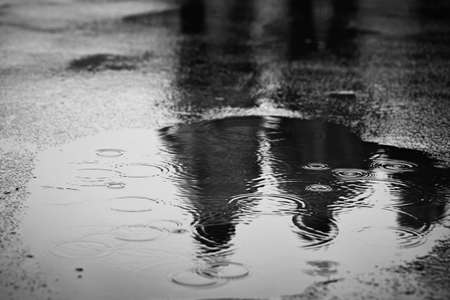 walking in the rain: Puddle of water in rain - selective focus