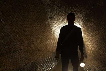 taschenlampe: Silhouette Mann in unterirdischen alten Kl�ranlage Lizenzfreie Bilder