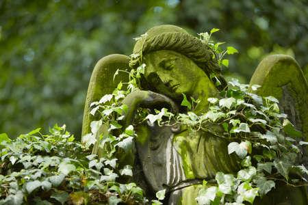 Sad angel statue on old cemetery  photo