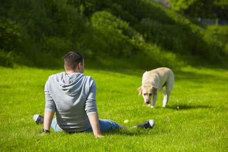 dog park: Young man with his dog on meadow.
