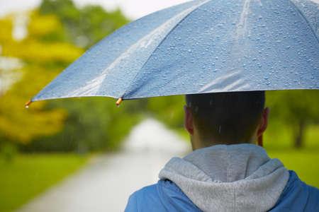 uomo sotto la pioggia: Giornata di pioggia - giovane uomo con l'ombrello