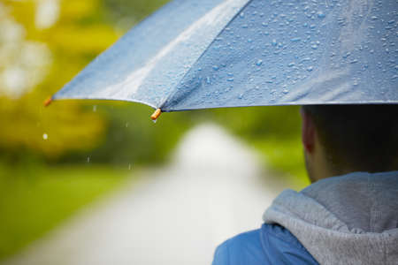 bad weather: Young man with umbrella - selective focus on drop