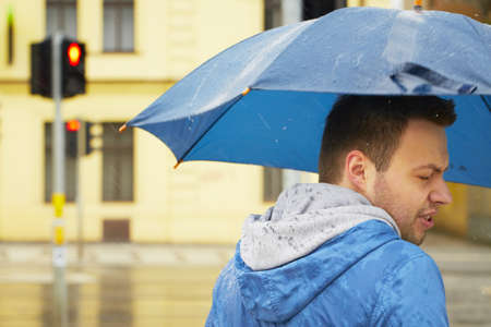 Rainy day - young man with umbrella  photo