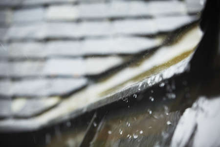 Old tiled roof in heavy rain - selective focus