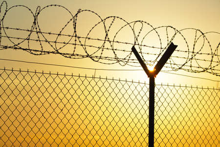 Fence covered with barbed razor wire  photo
