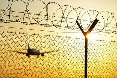 barbed wire fence: Airport at the sunset - security system Stock Photo