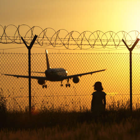 barbed wire fence: Airport at the sunset - unrecognizable person Stock Photo