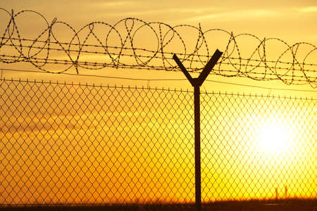 industry moody: Fence covered with barbed razor wire