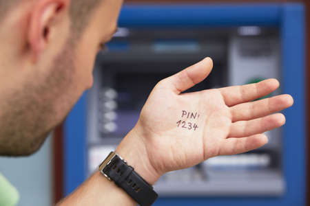 bad idea: Man look at the simple PIN code written on the palm  Stock Photo