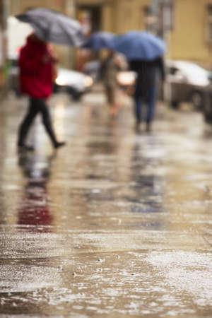 lluvia paraguas: Calle de la ciudad bajo una intensa lluvia - enfoque selectivo