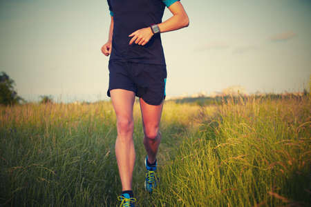 man legs: Young man is running on summer meadow - lovely sunset light