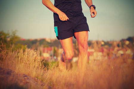 hombre deportista: Hombre joven que se ejecuta en prado de verano - la luz del sol hermosa