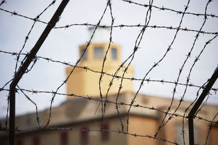 Prison - barbed wire in front of the guard tower - selective focus Standard-Bild