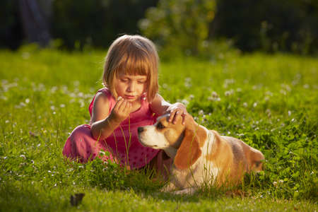 Kleines Mädchen mit Hund in den Garten