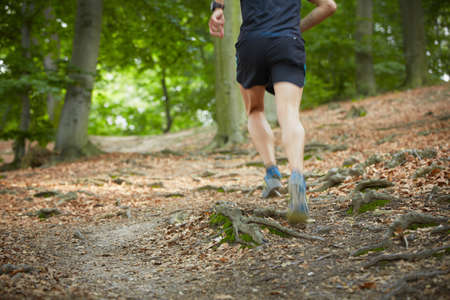 individual sport: Young man is running in forest - selective focus - blurred motion