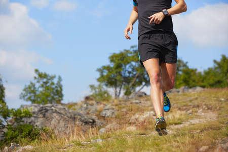 atleta corriendo: Hombre joven que se ejecuta en la naturaleza - el enfoque selectivo Foto de archivo