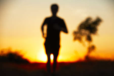 Young man is running at the sunset - defocused  photo