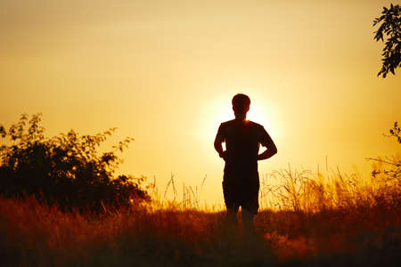 sun lit: Young man is running at the sunset - back lit