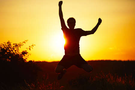 Freedom and victory - young man is jumping in nature - back lit Stock Photo - 21066000
