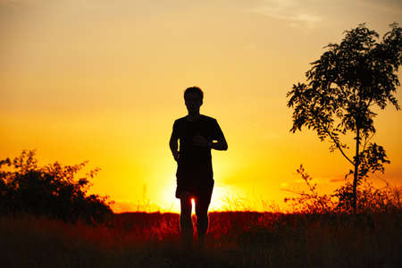 back training: Young man is running at the sunset - back lit