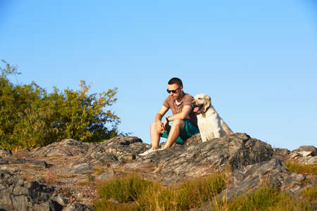 dog rock: Young man with his yellow labrador retriever in nature