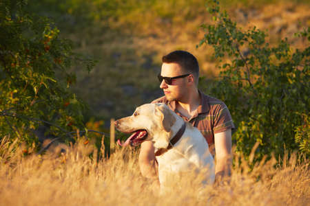 Young man with his yellow labrador retriever in nature - selective focus Фото со стока