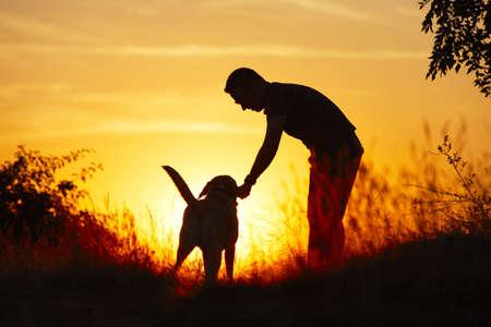 obedience: Hombre joven con su perro labrador de color amarillo en la naturaleza - y retroiluminaci�n