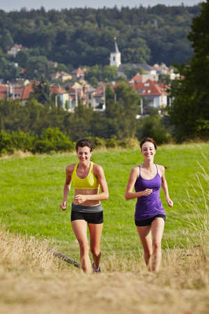 crosscountry: Two girls are running in nature - selective focus Stock Photo