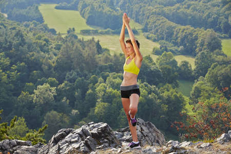 Young woman is meditating on top of the hill. Imagens - 21413790