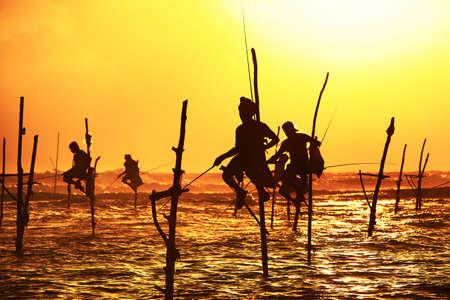 pescador: Siluetas de los pescadores artesanales en el atardecer cerca de Galle en Sri Lanka Foto de archivo