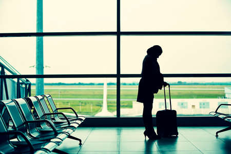 alone person: Woman with trolley is waiting in terminal of airport. Stock Photo