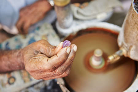 polishing: Craftsman is showing moonstone. It is one of the gems found in Sri Lanka. - Selective focus