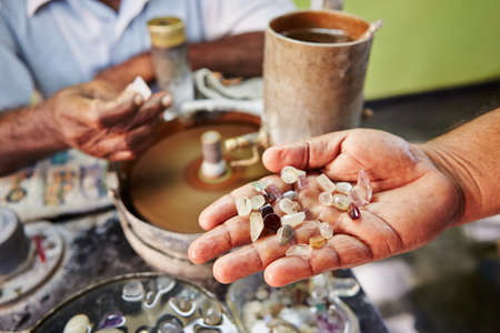 sri: Craftsman is showing moonstone. It is one of the gems found in Sri Lanka. - Selective focus
