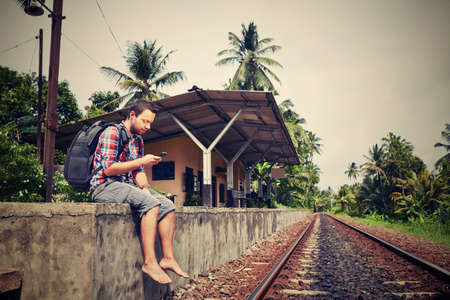 directions: Young traveler with mobil phone in the railway Stock Photo