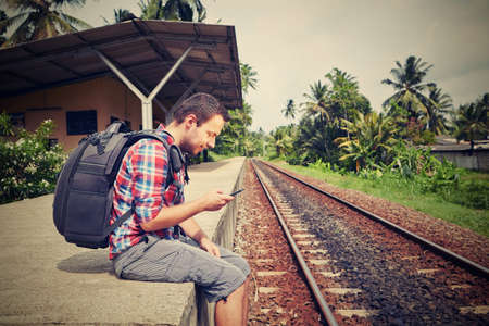 Young traveler with mobil phone in the railway Stock Photo