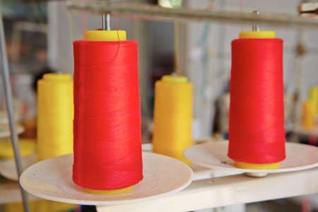 sartorial: Red spools of textile at manufacturing machine