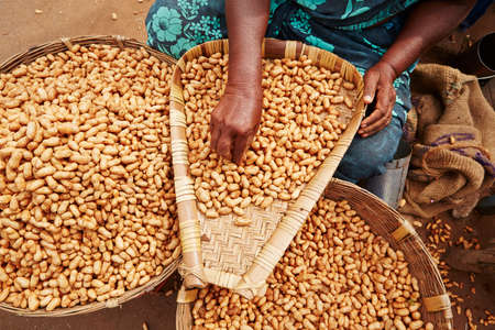 Woman with piles of peanuts on the street market in India. photo