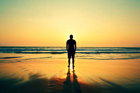 Silhouette of young man on the beach at sunset.  Stock Photo