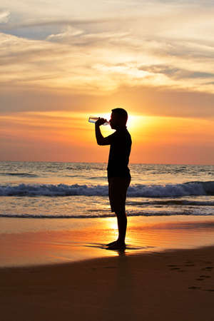 Man in drinking water at the sunset. photo