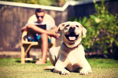 De mens is ontspannen op de tuin met zijn hond.