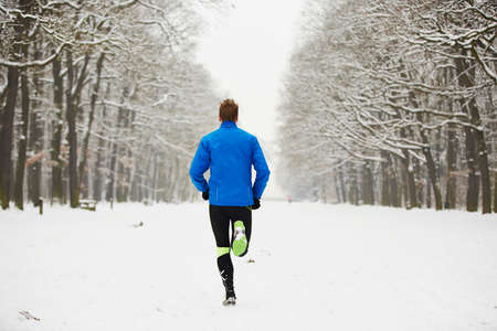 Young runner in winter jogging in park. Standard-Bild