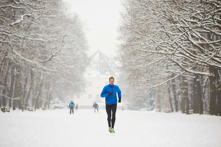 cold weather: Young runner in winter jogging in park. Stock Photo