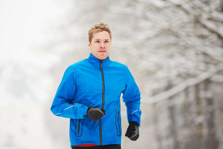 Young runner in winter jogging in park. photo