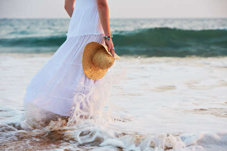 Pretty woman at sunset on the beach