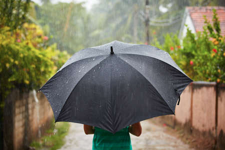 Frau mit schwarzen Regenschirm in schweren regen Standard-Bild - 26817394