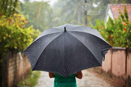 heavy rain: Woman with black umbrella in heavy rain