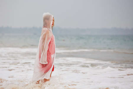 Young woman on the beach in heavy rain photo