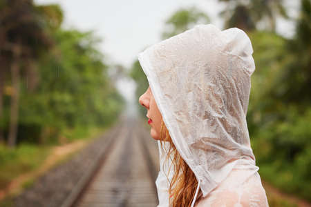 Young woman on the trip in heavy rain photo