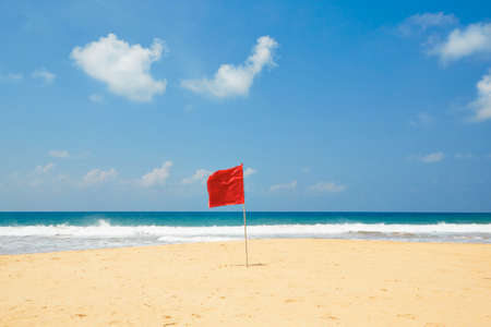 Warning flag on the beach. Swimming is dangerous in sea waves.